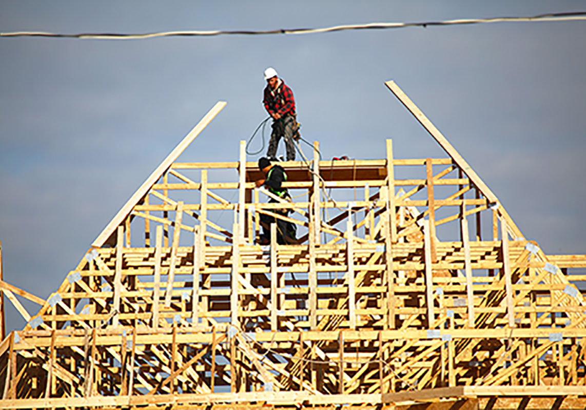 Vaughan, Ontario, Canada - October 14, 2016: Two roofers standing on top of the new roof frame for a new house. Construction site of new detached houses being built in Vaughan - Major MacKenzie Drive West and Via Romano Blvd (Patterson Community)